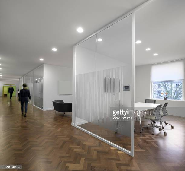 Meeting rooms enclosed behind a glass wall. AxiCom Office, London, United Kingdom. Architect: MZC+, 2019.