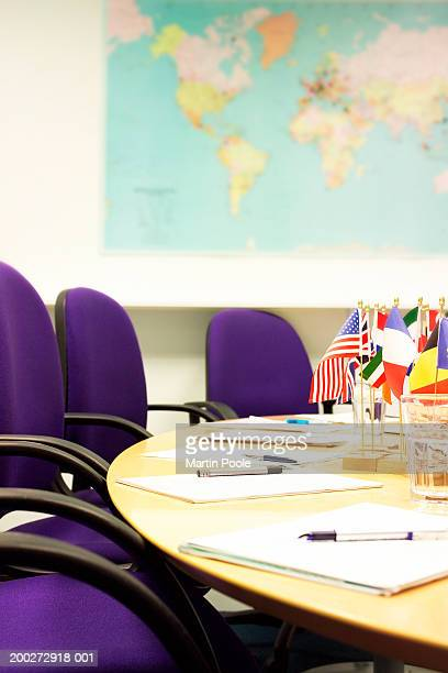 Meeting table with multi-national flags at centre, world map on wall