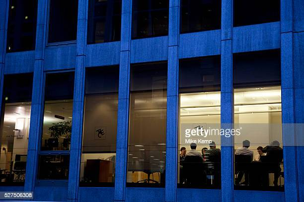 A meeting takes place at an office building in London Businessmen in discussion illuminated at night
