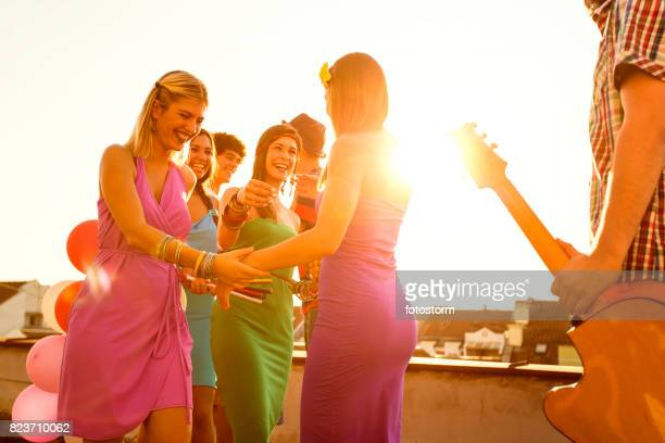 meeting with friends at rooftop party - welcoming guests stock photos and pictures