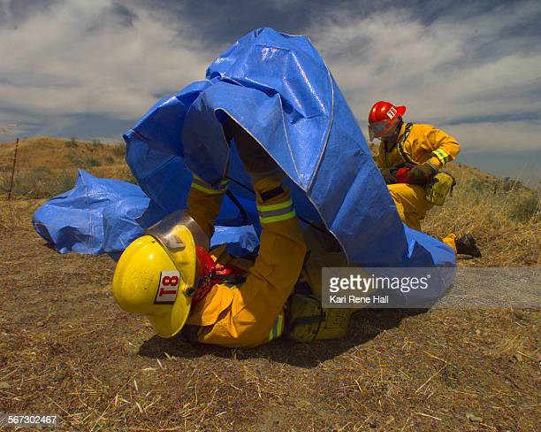 MEFireshelter2KRH5/6/97Engineer Doug Skinner from Anaheim Fire Department pulls a plastic tarp over himself to simulate a fire blanket in a dynamic...