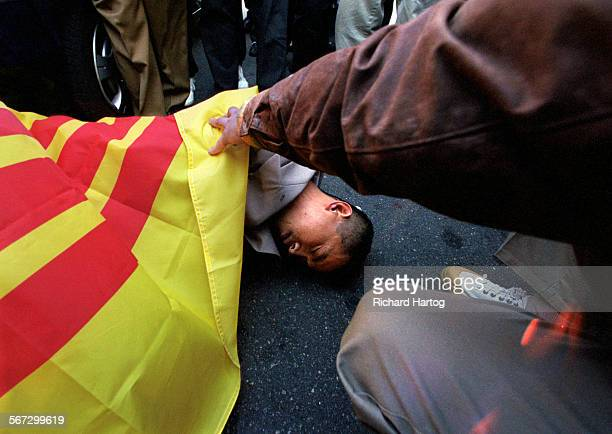 MEFlagFlagRH––021099––Surrounded by protestors media and almost no supporters shop owner Truong Van Tran lies motionless on the ground after being...