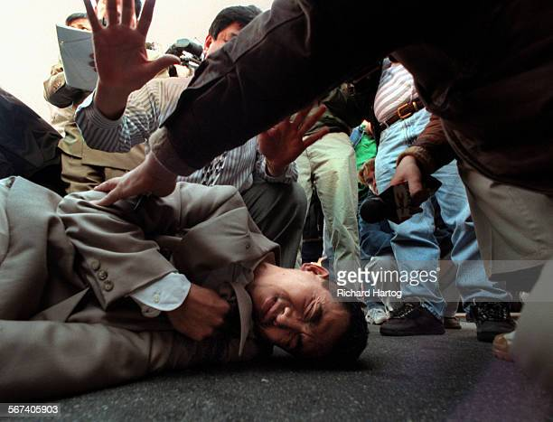 MEFlagOn GroundRH––021099––Surrounded by protestors media and almost no supporters shop owner Truong Van Tran lays motionless on the ground after...
