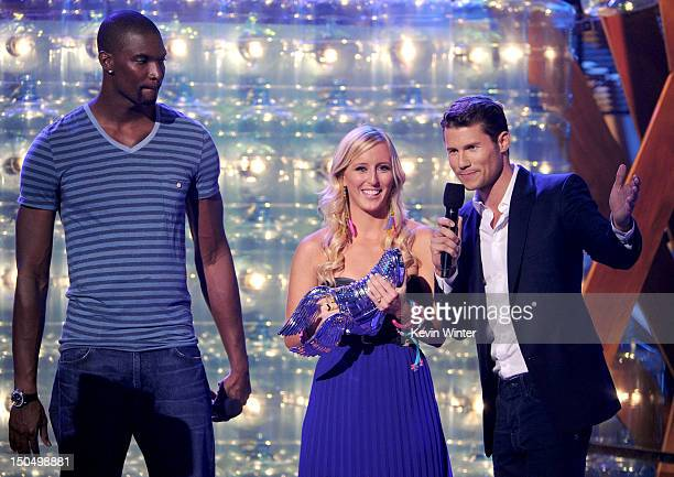 Meg Bourne accepts award from NBA player Chris Bosh and actor Jason Dundas onstage during the 2012 Do Something Awards at Barker Hangar on August 19,...