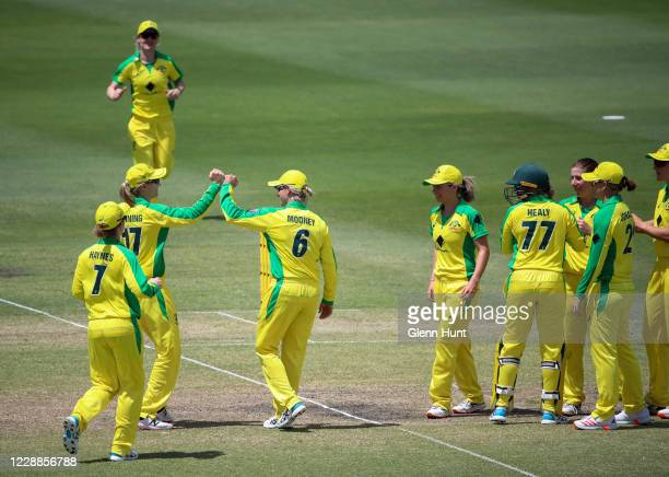 Meg Lanning and Beth Mooney of the Australia celebrate with team mates after getting the wicket of Jessica Kerr of New Zealand leaves the field after...