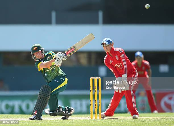 Meg Lanning of Australia hits a six as wicketkeeper Amy Jones of England looks on during game one of the International Twenty20 series between...