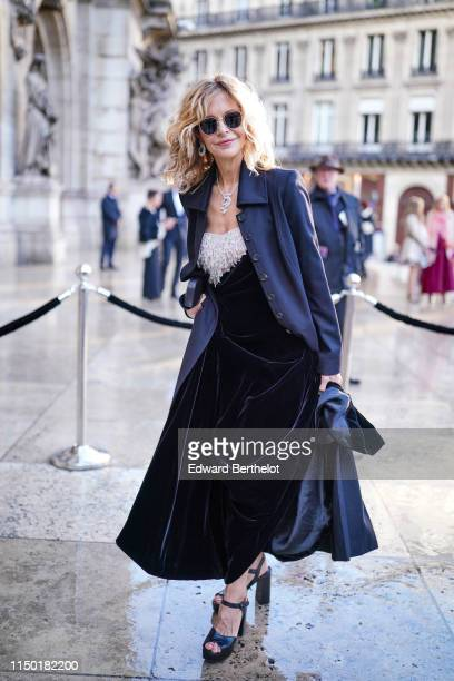 Meg Ryan wears sunglasses earrings a glittering necklace a lustrous navy blue jacket a black velvet dress with a glittering beaded upper part black...