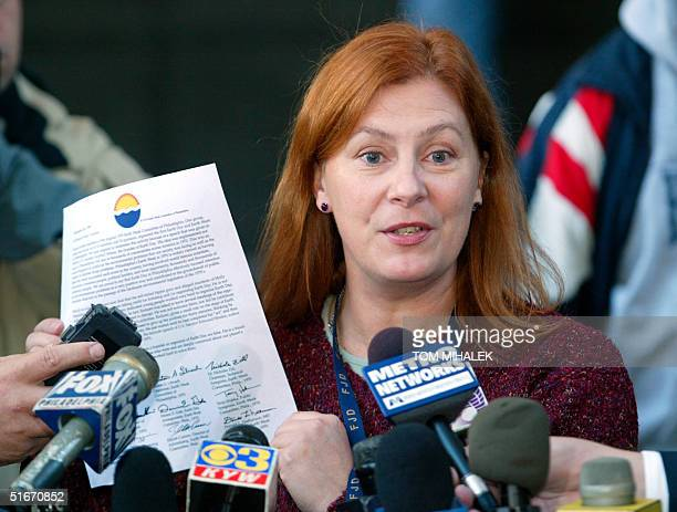 Meg Wakeman the sister of Holly Maddux holds up a letter at a press conference 14 October 2002 written and signed by the nine founding members of...
