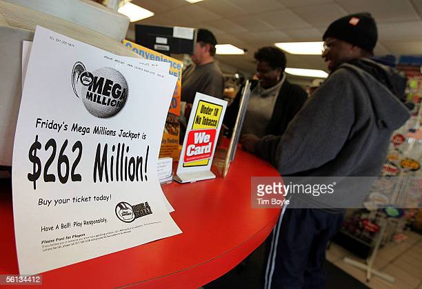 Mega Millions lottery players line up for tickets beyond signage relating to such at a gas station which is located on the border of the state of...