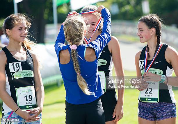 Megan Alberding of Yarmouth receives her medal from elite athlete Jordan Hasay of Portland Oregon as Alicia Lawrence of Cape Elizabeth left and...