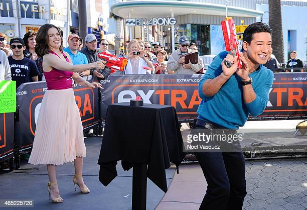 Megan Boone and Mario Lopez play with toy guns at Extra at Universal Studios Hollywood on March 4 2015 in Universal City California