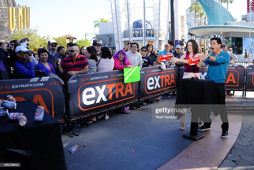 Megan Boone and Mario Lopez play with toy guns at 'Extra' at Universal Studios Hollywood on March 4, 2015 in Universal City, California.