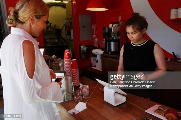 Megan DeWitt, left, waits to use her Apply Pay to pay for her drink as Coffee Educator Christina Busler rings her up in Ritual Coffee off of Octavia...