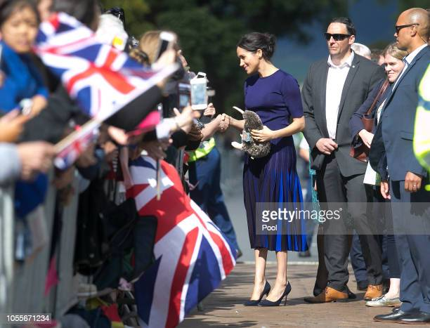 Megan Duchess of Sussex accepts gifts from the crowds during a walkabout at Government Gardens on October 31 2018 in Rotorua New Zealand The Duke and...