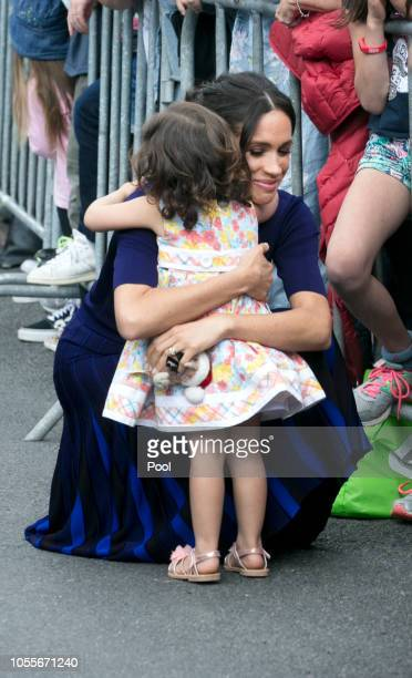 Megan, Duchess of Sussex hugs a little Catalina Rivera who got through the railings during a walkabout at Government Gardens on October 31, 2018 in...