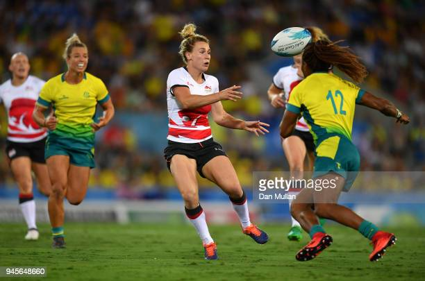 Megan Jones of England offloads under pressure from Ellia Green of Australia during the Rugby Sevens Women's Pool B match between Australia and...