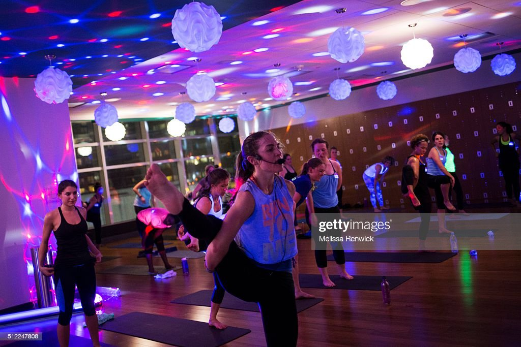 Megan Leach teaches a black light yoga class at Hard Candy Fitness during a 'sweat working' event for women. : News Photo