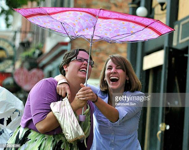 Megan Molnar left of Canton and her friend Megan Kobuck of Alexandria Virginia lose control of their umbrella in Fells Point Baltimore Marylandy as...