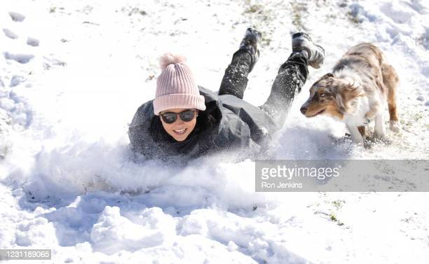 Megan Pennartz and her dog Jensen go sledding after a snow storm February 15, 2021 in Fort Worth, Texas. Winter storm Uri has brought historic cold...
