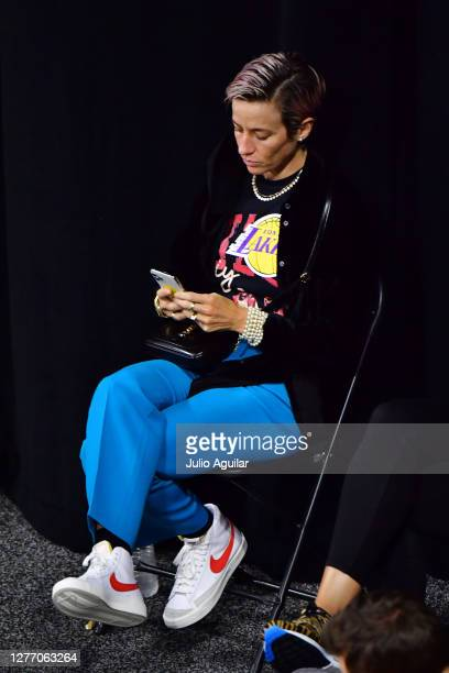 Megan Rapinoe looks at her phone during a timeout in the first half of Game Three of the Third Round playoff between the Seattle Storm and the...