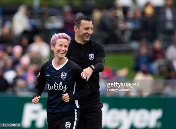 Megan Rapinoe of Reign FC smiles with Reign FC coach Vlatko Andonovski after being subbed out in the second half of the game at Cheney Stadium on...