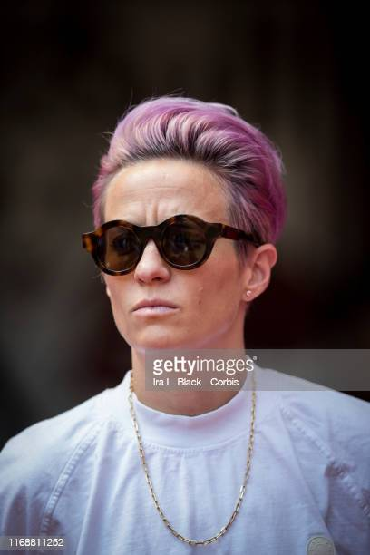 Megan Rapinoe of Seattle Reign FC looks ahead with pink hair wearing sunglasses as she stands in on the sideline due to an injury before the National...