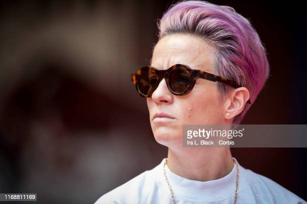 Megan Rapinoe of Seattle Reign FC looks intent with pink hair wearing sunglasses as she stands in on the sideline due to an injury before the...