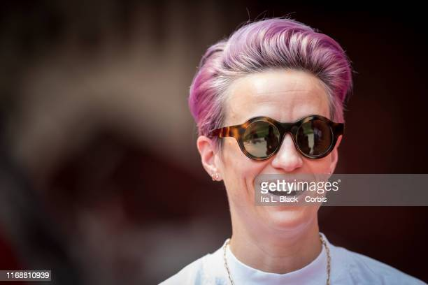 Megan Rapinoe of Seattle Reign FC smiles with pink hair wearing sunglasses as she stands in on the sideline due to an injury before the National...
