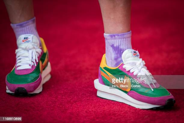 Megan Rapinoe of Seattle Reign FC wearing rainbow Nike sneaker as she stands in on the sideline due to an injury before the National Women's Soccer...
