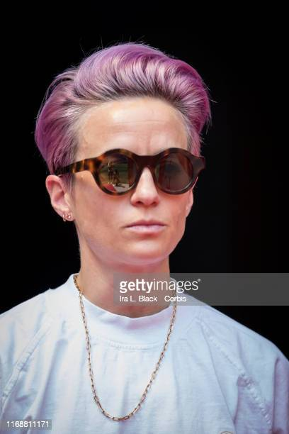 Megan Rapinoe of Seattle Reign FC with pink hair and sunglasses stands in on the sideline due to an injury before the National Women's Soccer League...