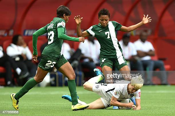 Megan Rapinoe of the United States is knocked down by Ngozi Ebere and Ukpong Sunday of Nigeria in the first half in the Group D match of the FIFA...
