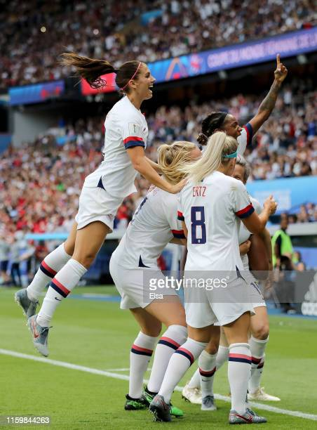 Megan Rapinoe of the United States is swarmed by teammates Alex Morgan and Julie Ertz after she scored a goal in the first half against France during...