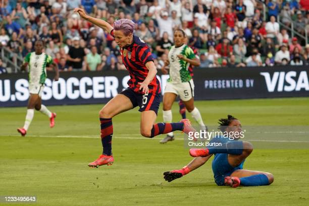 Megan Rapinoe of the United States leaps over goalkeeper Tochukwu Oluehi of Nigeria during the first half of their WNT Summer Series game at Q2...