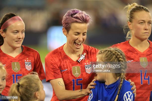 Megan Rapinoe of the United States stands on the field with a young fan before their game against Korea Republic at Bank of America Stadium on...