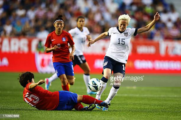 Megan Rapinoe of the USA is tackled by Kim Narae of Korea Republic during their game at Red Bull Arena on June 20 2013 in Harrison New Jersey