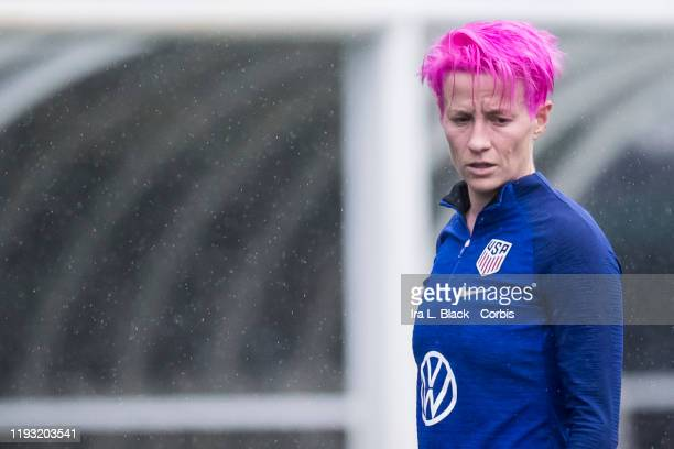 Megan Rapinoe of United States with pink hair walks back to the locker room with rain falling around her during the training session prior to the...