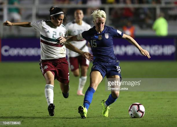 Megan Rapinoe of USA goes after a ball against Kenti Robles of Mexico during the Group A CONCACAF Women's Championship at WakeMed Soccer Park on...