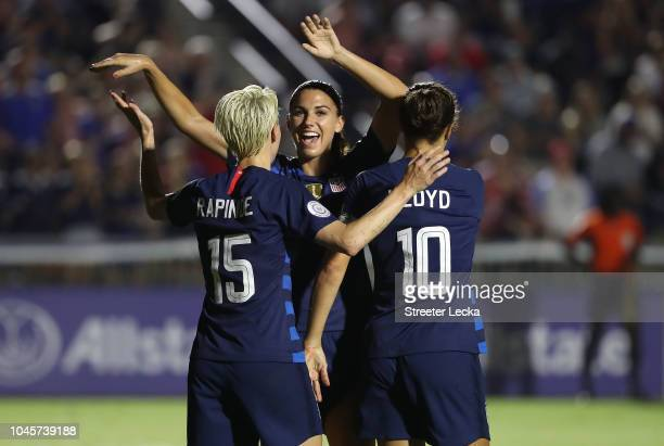 Megan Rapinoe reacts after scoring a goal as she celebrates with teammates Alex Morgan and Carli Lloyd of USA against Mexico during the Group A...