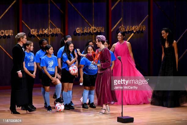Megan Rapinoe speaks onstage alongside Ali Krieger Ashlyn Harris and the Mott Hall Girls soccer team at the 2019 Glamour Women Of The Year Awards at...