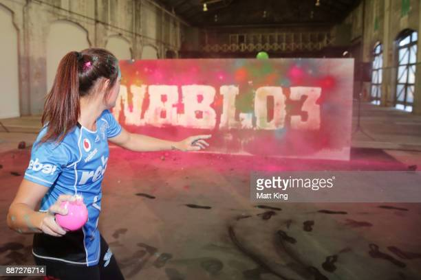 Megan Schutt of the Adelaide Strikers throws chalk filled Christmas baubles at a white backdrop during the 201718 WBBL Women's Big Bash League season...