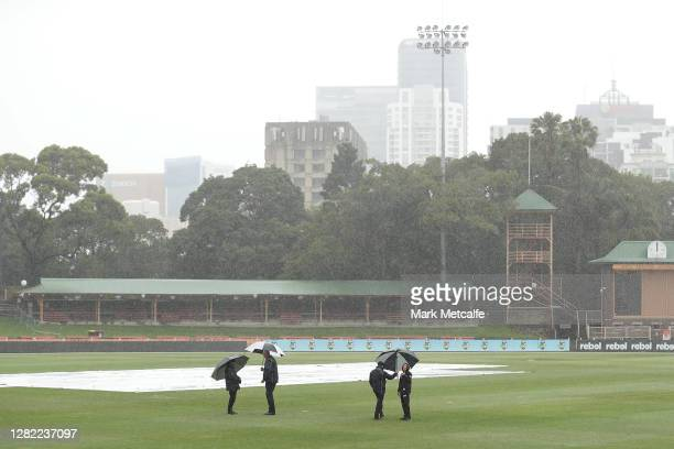 Megan Schutt of the Strikers and the match officials inspec the pitch during a rain delay during the Women's Big Bash League WBBL match between the...