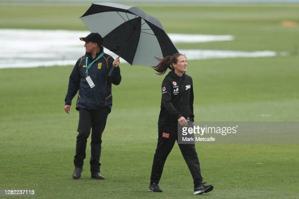 Megan Schutt of the Strikers and the match officials inspect the pitch during a rain delay during the Women's Big Bash League WBBL match between the...