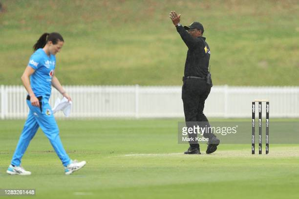 Megan Schutt of the Strikers leaves the field as the umpire calls for the covers during a rain delay during the Women's Big Bash League WBBL match...