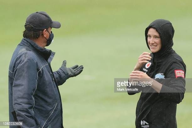 Megan Schutt of the Strikers talks to a member of the ground staff during a rain delay during the Women's Big Bash League WBBL match between the...