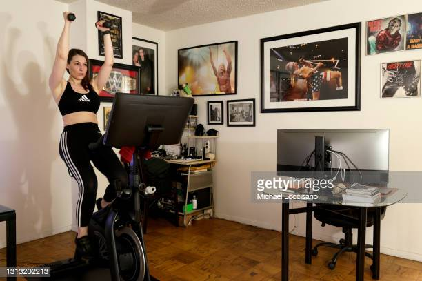 Megan Thompson works out on her SoulCycle exercise bike on April 18, 2021 in New York City. There is a competitive business war between indoor...