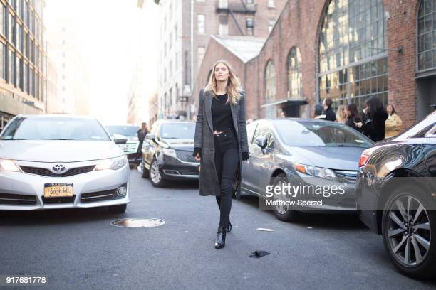 Megan Williams is seen on the street attending Zadig Voltaire during New York Fashion Week wearing a long grey wool coat with torn black sweater and...
