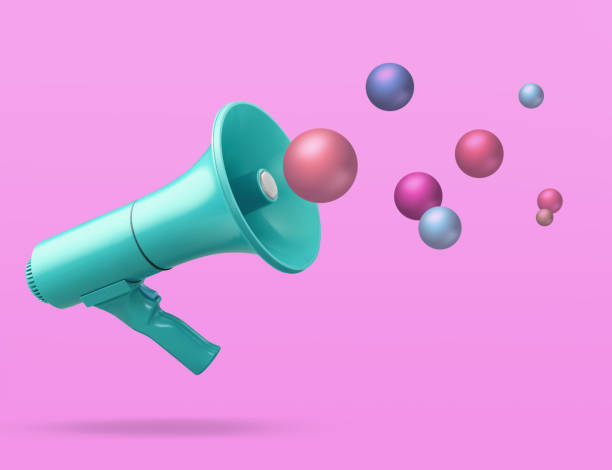 Megaphone on pink background with conceptual colourful balls spheres in air