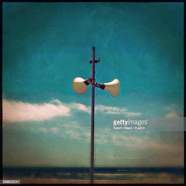 Megaphones Attached To Electric Pole Against Cloudy Sky