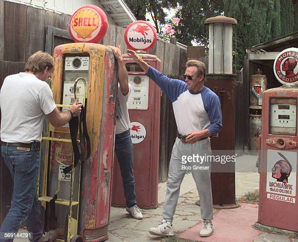 MEGaspumpsmoving1BG3Jun97––David Chorak wearing sunglasses to hide the tears reaches out to help as movers take the lst gas pump of his 25 year...