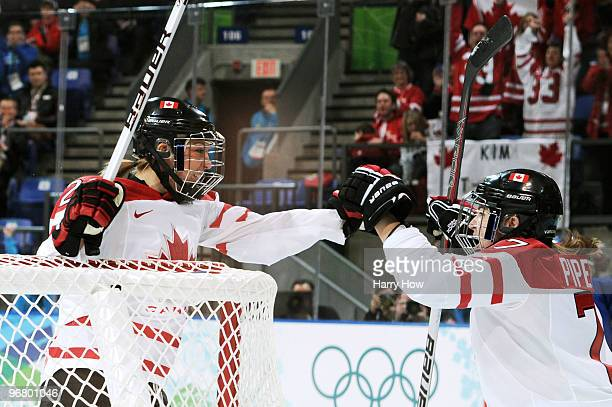 Meghan Agosta of Canada is congratulated by teammate Cherie Piper after scoring the opening goal during the ice hockey women's preliminary game...